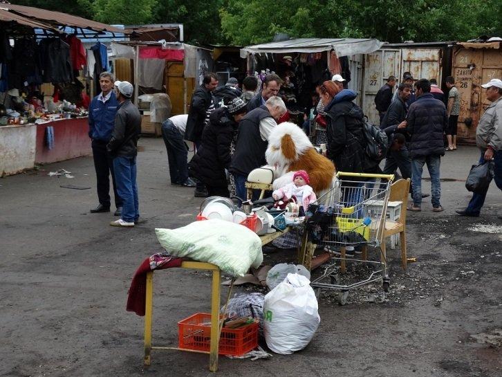 Товары на прилавке и посетители рынка